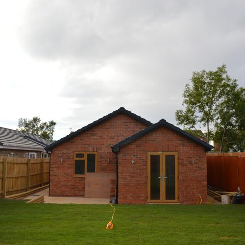 rear house view of garden water sprinkler and brick built house