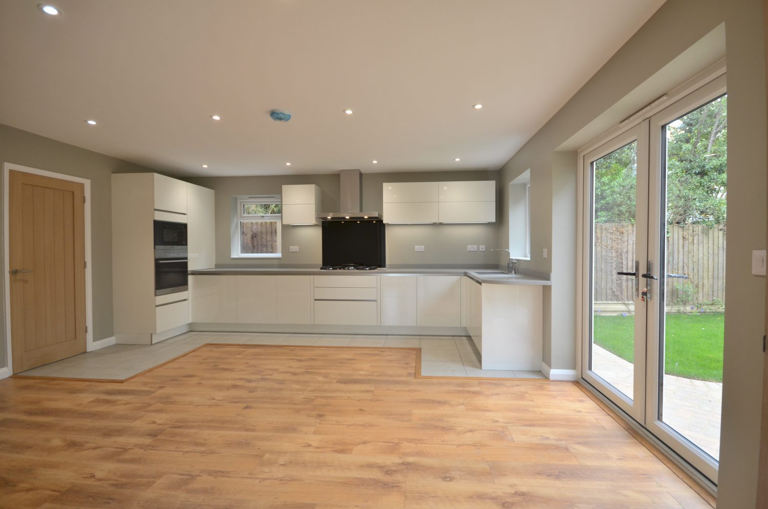 Large modern kitchen with laminate floor and high quality appliances