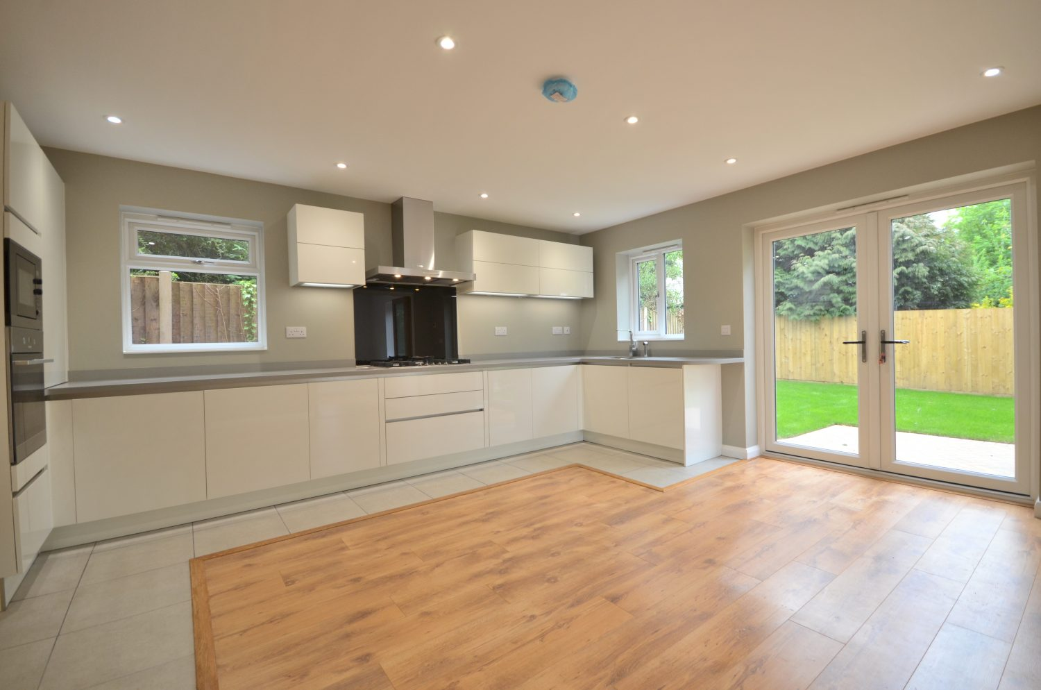 Bespoke Kitchen with a wooden floor joining on to a garden from George Staffordshire Developments Ltd