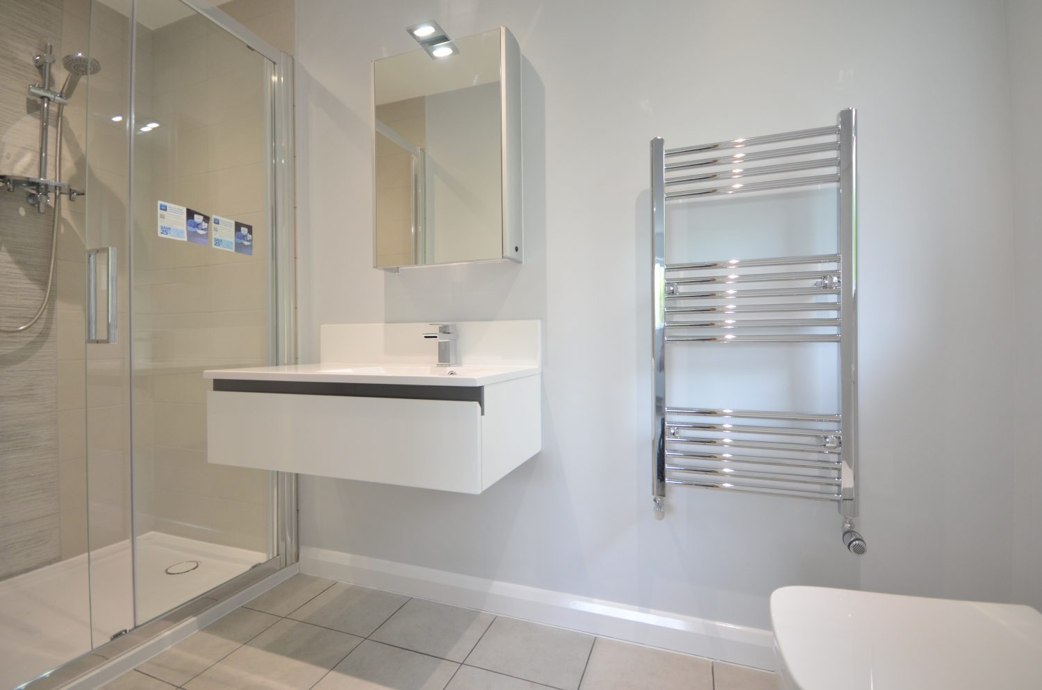 modern bathroom suite with shower bathroom cabinet sink and towel radiator