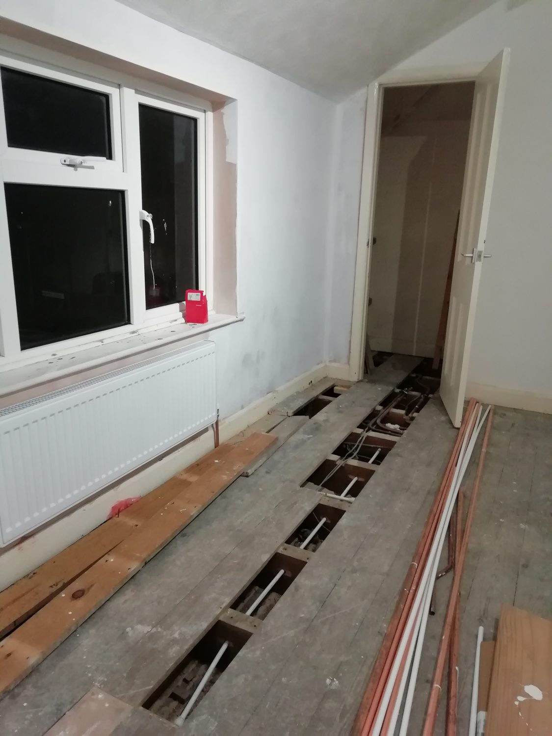installing new central heating system floor boards lifted