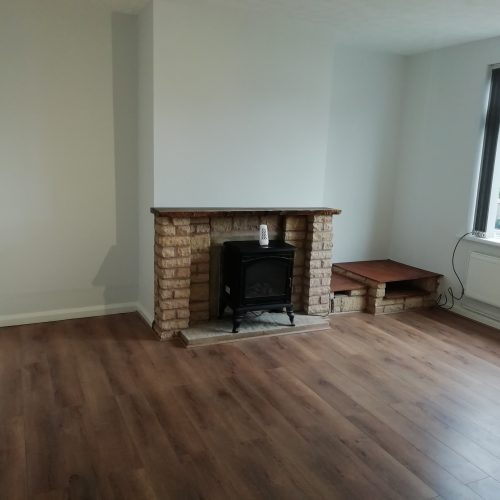 traditional living room with fireplace stone fire surround and laminate floor