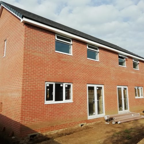 brick and block semi detached houses under construction with drainage and trenches