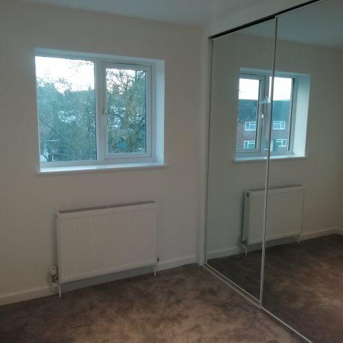 bedroom with mirrored sliding wardrobe UPVC window and radiator