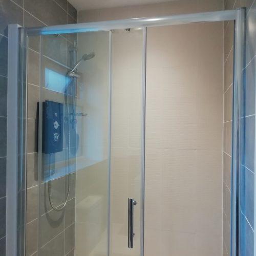 tiled modern sliding door shower enclosure with electric shower