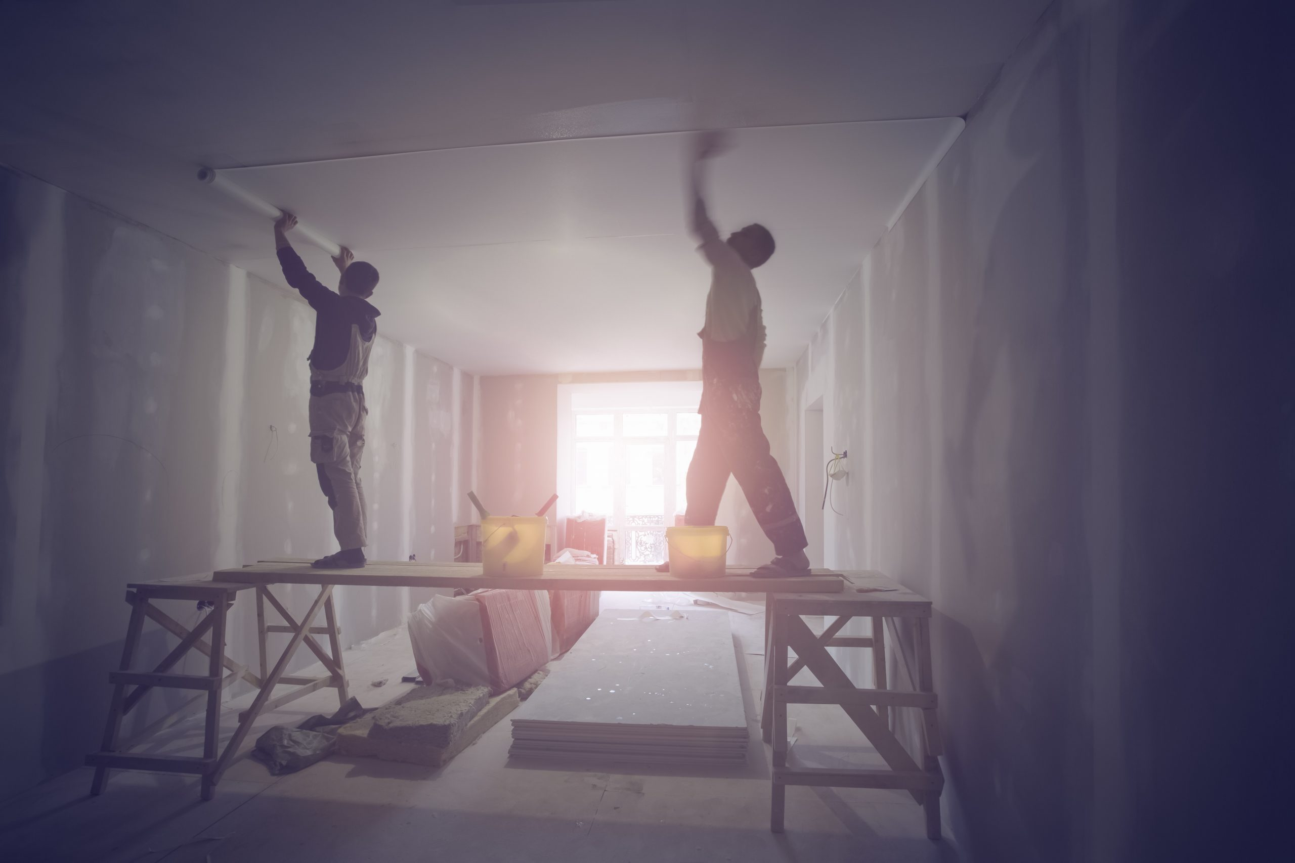 Workers are installing ceiling from wooden platform in apartment is under construction, remodeling, renovation, extension, restoration and reconstruction.