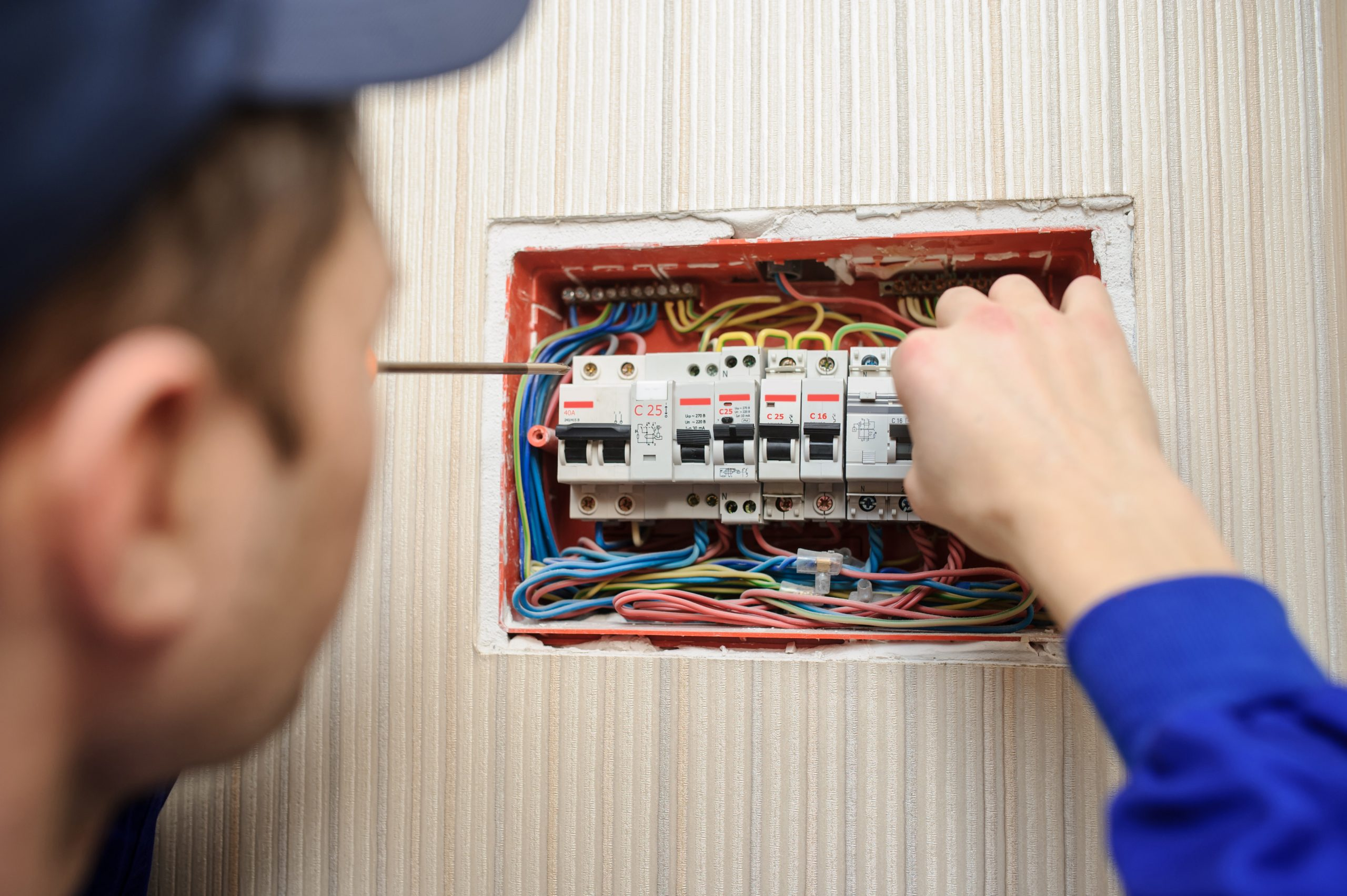 Man Fixing a Fuse Box with Trip Switches