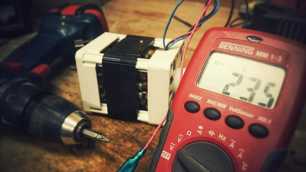 Red Multimeter next to a drill on a desk being used to test electrics