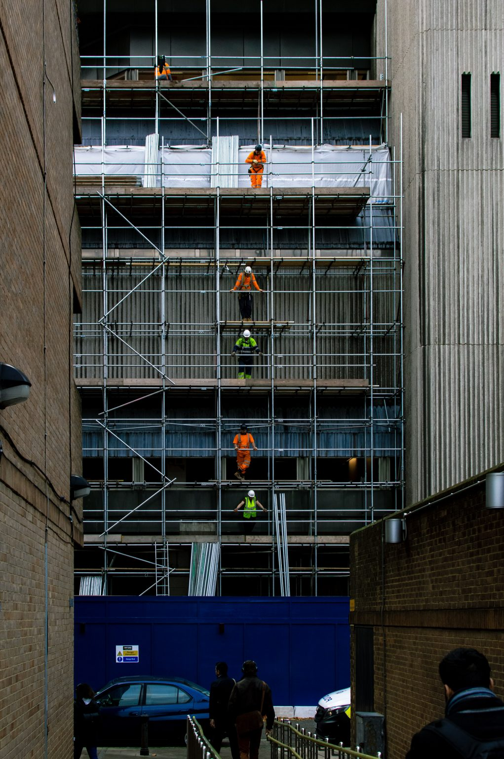 Builders On Top Of Each Other On Levels Of Scaffolding